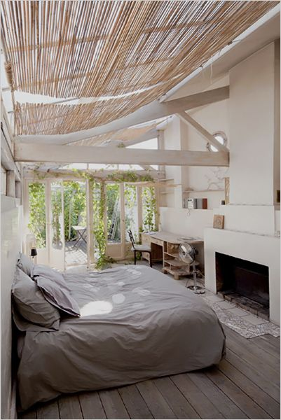 An ideal bedroom: fire, ceiling light, terrace, ivy invasion.