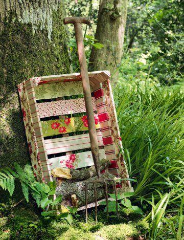 Une cagette en bois recouverte de tissus à fleurs, collés à la colle à bois