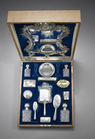 A silver dressing set, Fabergé and others, late 19th century comprising: a dressing mirror, bearing spurious Fabergé marks, a small round dish, Fabergé, Moscow, circa 1900; 2 perfume bottles, a silver and glass box, a brush, a hand-mirror, and a circular box, each bearing Fabergé marks; together with an oval bowl, Kurliukov, Moscow, circa 1890, and a beaker, Paris, maker's mark PQ in lozenge, circa 1890; all in a fitted case, stamped with retailer's name beneath the Imperial warrant.♥≻★≺♥