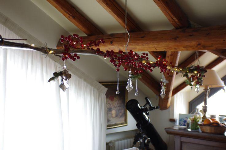 Decorazione natalizia sospesa ,raccolta attorno ad un ramo lungo di albero