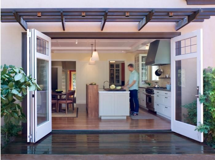 Officially in love with this indoor-outdoor kitchen dining space. Wide doorway for minimal separation between inside and out; galley kitchen with an island separating the cooking from the dining, but still open for socializing.
