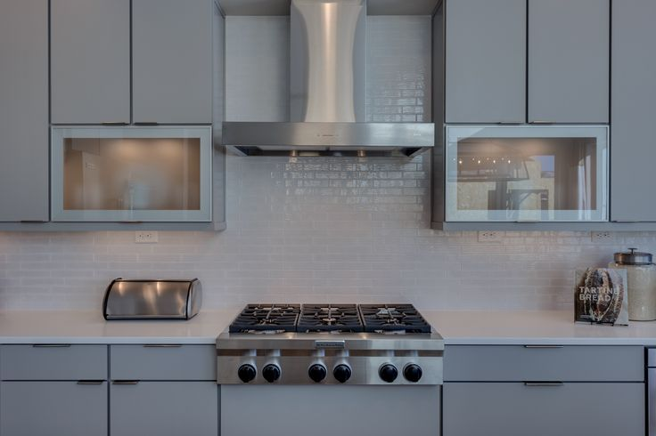 Kitchenaid 6-burner gas cooktop with venthood above and Arctic White brick tile backsplash are a focal point in the kitchen!