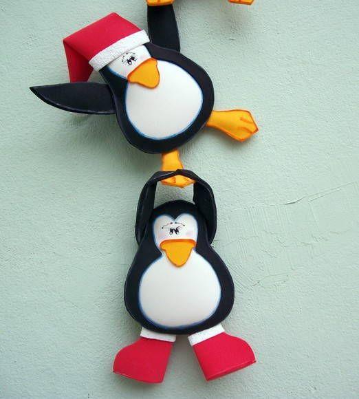 """O trio de pinguins faz a festa nesse Natal!!!    Divertidos, esses """"senhores"""" pegaram partes da roupa do Papai Noel... Cinto, bota, gorro.    Com essa guirlanda, você dá um toque de graça na decoração de Natal da sua casa!    Fica ótimo pendurado na porta de entrada, na parede do quarto das crian..."""