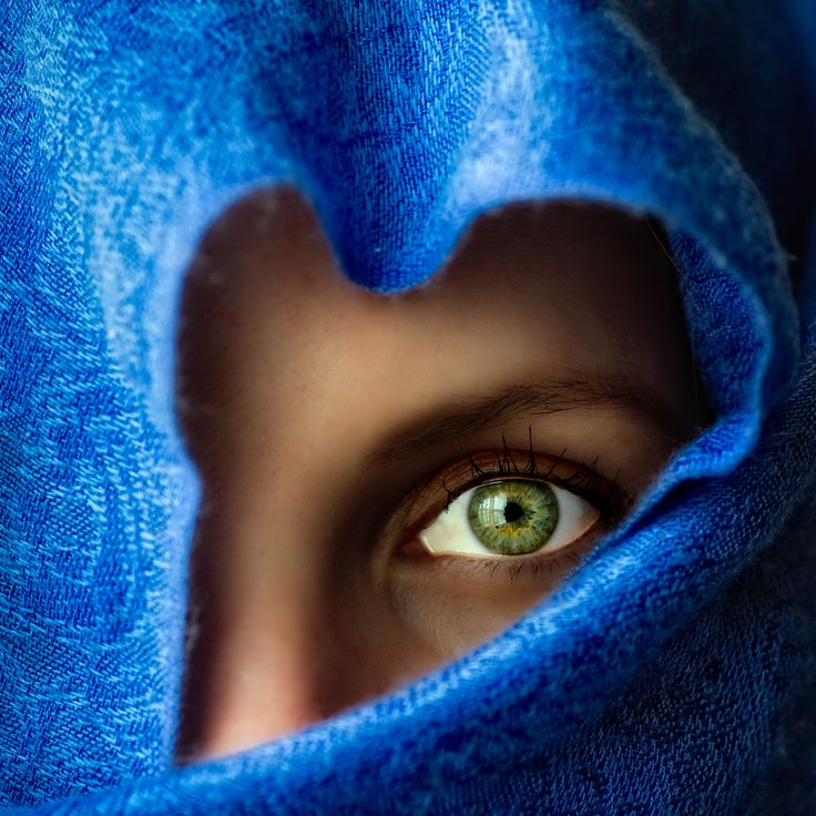close-up portrait of the gorgeous green eyes of a veiled woman.