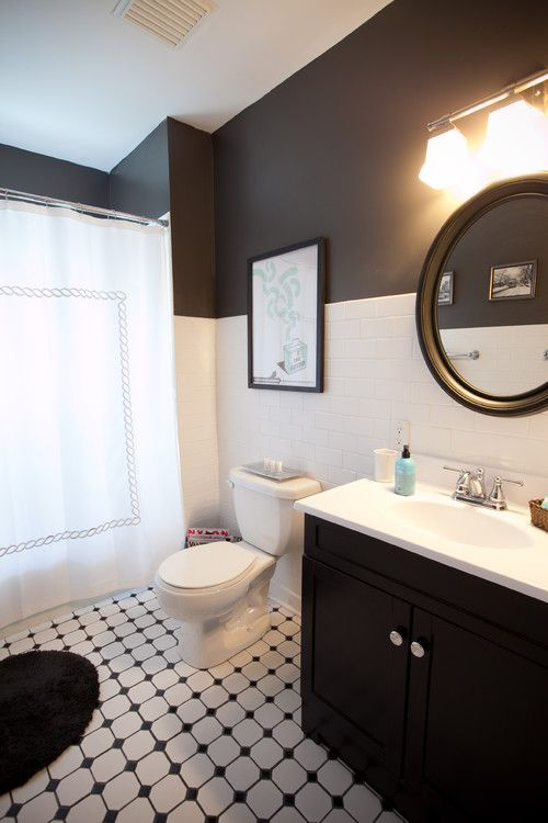 black cabinets are paired with black and white accented walls in this traditional bathroom