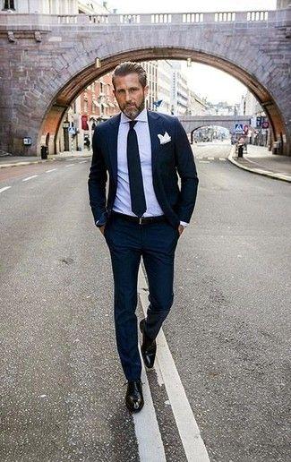 Utiliza un traje azul marino y una camisa de vestir violeta claro para rebosar clase y sofisticación. Para el calzado ve por el camino informal con zapatos derby de cuero negros.