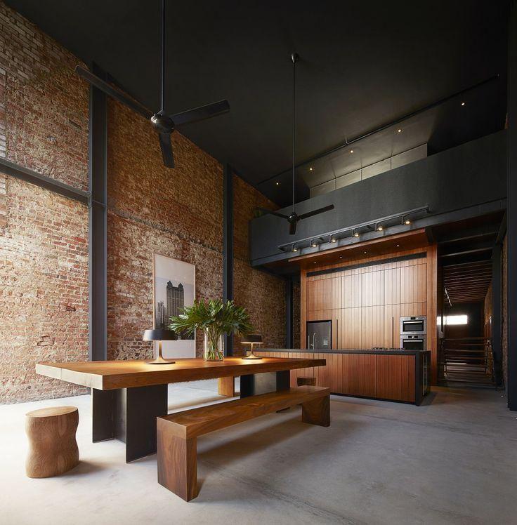 Loft com parede de tijolo á vista e detalhes arquitetônicos em preto.