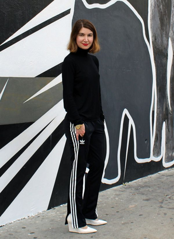 Street style look suéter preto, calça preta adidas e salto branco.