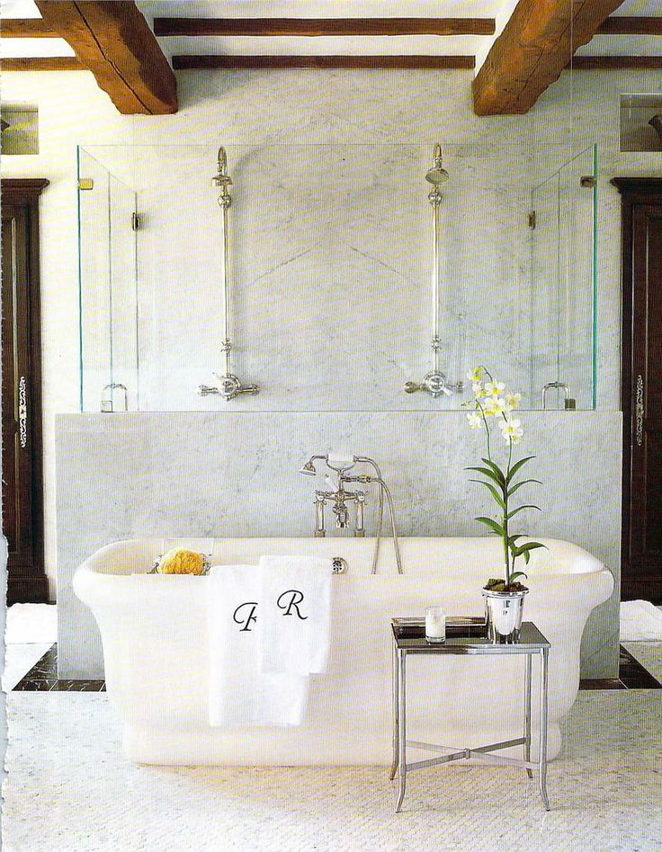 tub in front of open shower + marble half wall + rustic beams | Renea Abbott, Veranda Magazine: