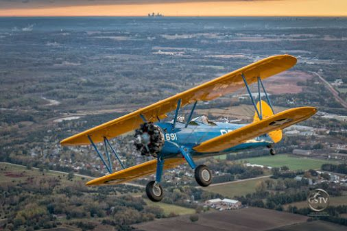 Boeing Stearman at Sunrise  On the horizon you can see the silhouettes of the high rise buildings in downtown Minneapolis and St. Paul, Minnesota.  Gazing Skyward TV - Google+