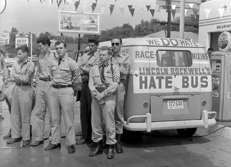 """George Lincoln Rockwell, center, self-styled leader of the American Nazi Party, and his """"hate bus"""" with several young men wearing swastika arm bands, stops for gas in Montgomery, Alabama, on May 23, 1961, en route to Mobile, Alabama. (AP Photo)"""