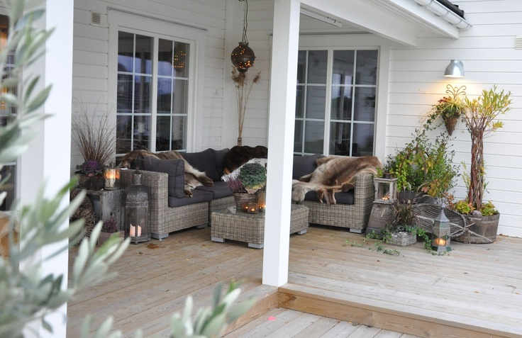 Beautiful fall porch with sectional, candles, fur, potted plants.