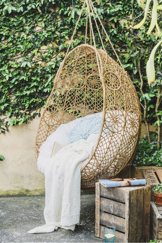 wicker egg shaped chair suspended in an outdoor space for relaxation