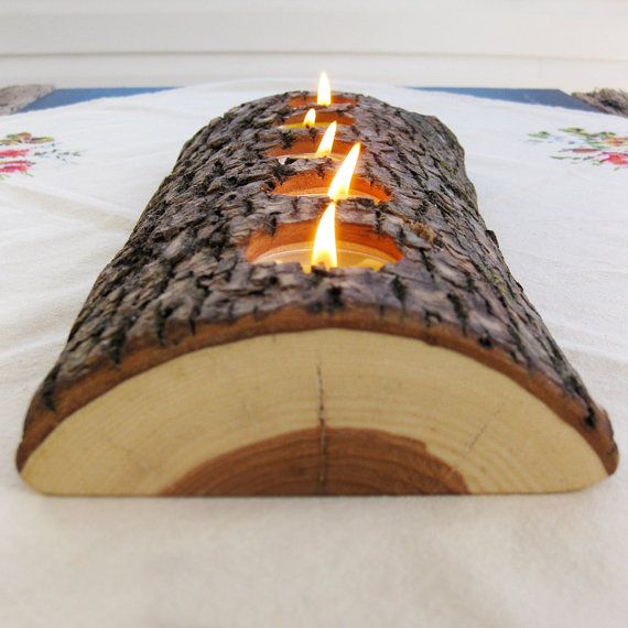 DIY wood tealight candle holder made from a found split log. It holds 5 candles and is wide, not tall, almost appearing to be set into the table.