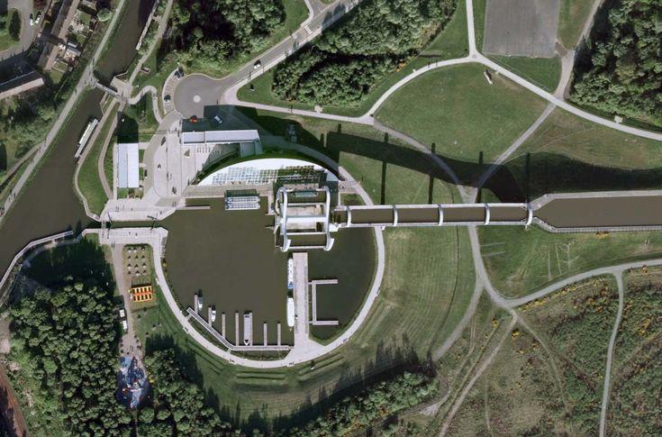 Roue de Falkirk, Ecosse. Vue aérienne, obtenue sur 'Google Earth'. L'ombre de l''Union Canal' met en évidence les 25 mètres de dénivellation avec le 'Forth and Clyde Canal'. La roue est en mouvement, les 2 caissons étant à peu près au même niveau.
