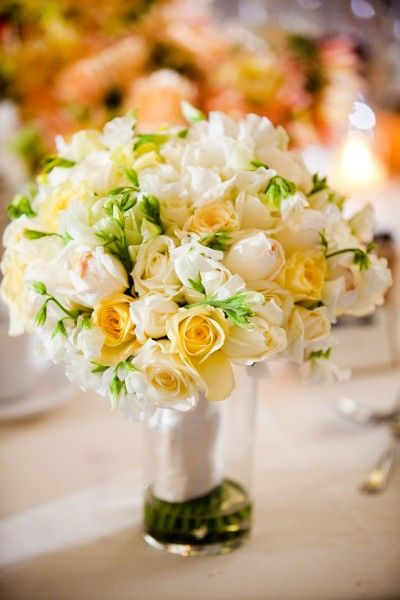 Pale yellow and white hand-tied bridal bouquet made with roses, garden roses, sweetpeas, and freesia