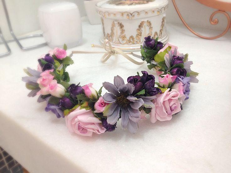 Coroa de flores confeccionada com flores em tecido e E.V.A, nas cores rosa, lilás e roxo. A base é uma tiara forrada com fio de camurça, portanto ajustável à qualquer cabeça.