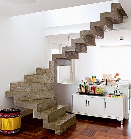 """A escada em """"L"""", que ocupava muito espaço e escurecia a sala, foi substituída por esta, em """"U"""", de concreto armado. """"A ideia era deixá-la leve e neutra. Em vez de revestimento, optamos pelo cimento queimado"""", diz a arquiteta Claudia Percego"""