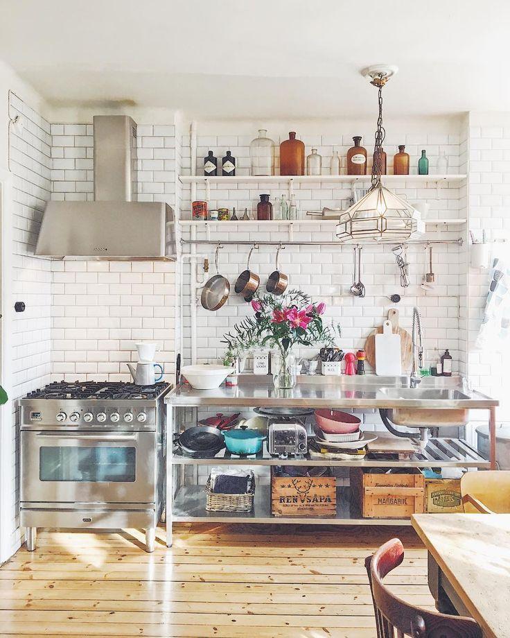 Edelstahl küche mit offenem regal vor weißer backsteinwand