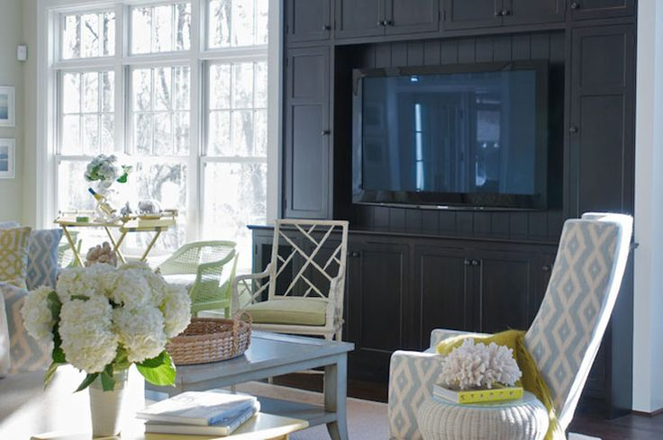 Gorgeous living room with black built-in media cabinet with beadboard paneling framing the mounted flat screen tv next to a wall of floor length windows with a tray table and white cane backed chair.
