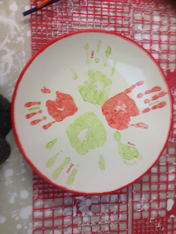 Two children painting their handprints on a fruit bowl at The Crafty Cafe