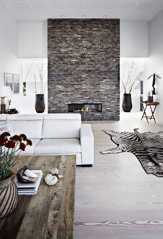 Vaalea moderni lattia, rustiikki sohvapöytä, puhdasta valkoista ja tiiliseinä.