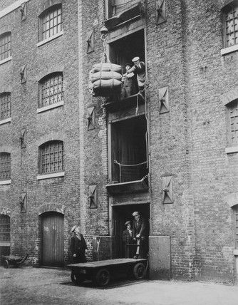 London, West India Docks 1900: Sugar being hoisted into warehouses.