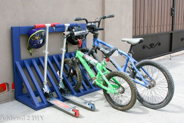 Build this simple bicycle rack with these free plans! It not only keeps bikes and scooters organized, but there's a place to hang helmets!