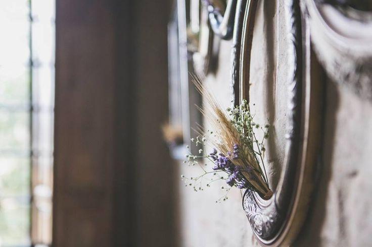 detalhes das molduras de madeira antigas que estavam na parede de tijolo atrás da mesa do bolo desse casamento com toques vintage onde o trigo e a lavanda foram personagens principais