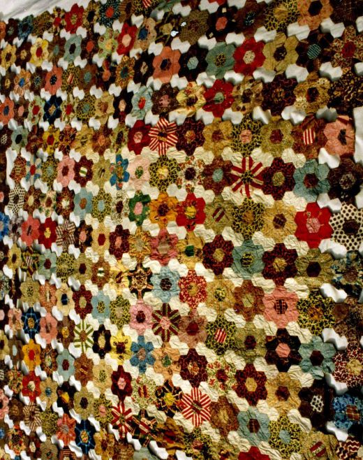 Hexagons Rosette Fragment. Hexagon rosettes fragment, made from various cotton prints dating from the 1840s -50s. Some of the rosettes are missing their joining hexagons. 190cm x 200cm. Quilt Museum and Gallery