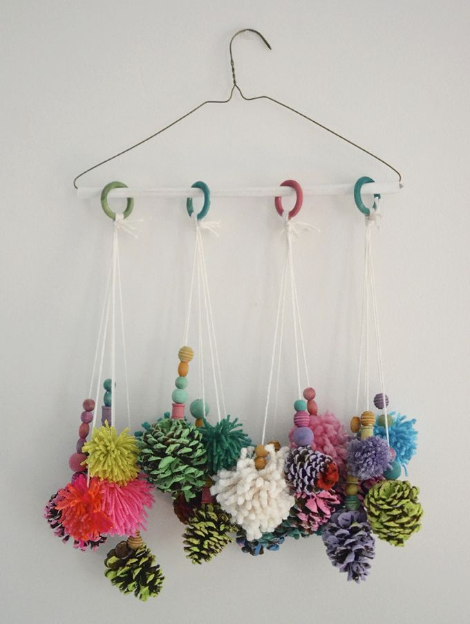 Kids make mobiles from painted pinecones and homemade pom-poms.