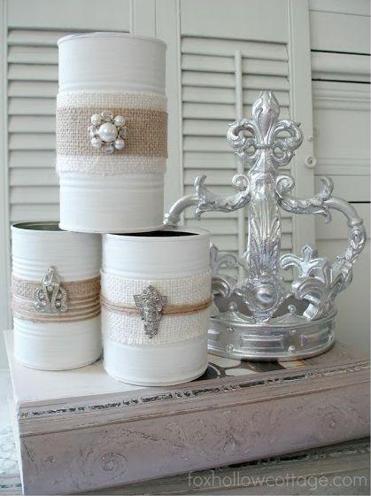 Latas pintadas de blanco adornadas con yute, rafia, en un estilo rústico y vintage.