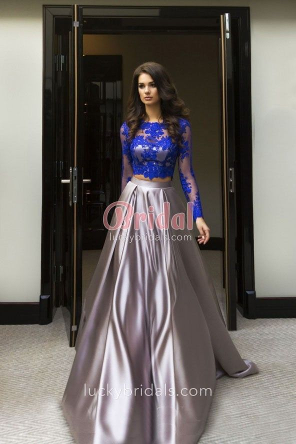 d66f18fafac This modern two-piece prom dress consists of a royal blue lace crop top  featuring illusion long sleeves
