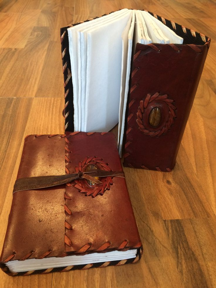 """Leather Bound Tiger Eye Journal. Compose your most precious thoughts or fanciful scribbles on linen/parchment paper surrounded by a luxurious leather cover. Polished tiger eye crowns the front of this intriguing journal. 120 blank pages. 5""""x7"""""""
