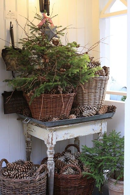Natural country winter celebration display with real evergreen sprigs & pinecones.  I really like this, but don't have the talent to pull it off.  :(