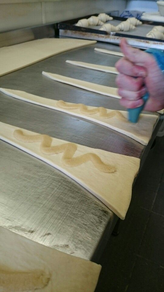 Marzipan being piped onto the croissant dough before being rolled into the desired shape.