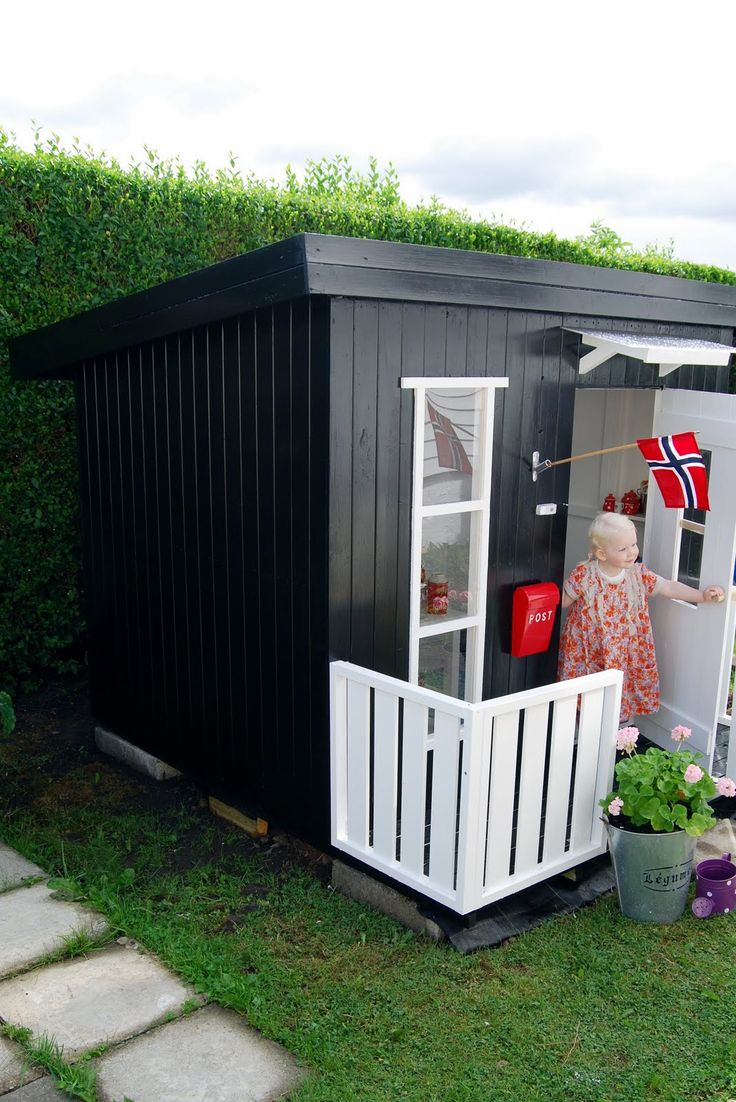 "Den gode feen: Velkommen inn i lekehuset Linda  (Norwegian for ""The Fairy Godmother: Welcome to Linda's toy house)  //  This eye-catching black & white playhouse in Norway complements the owner's full-size house which is painted white w/ a black door. It has charming details including a mailbox, flag & small flower garden  