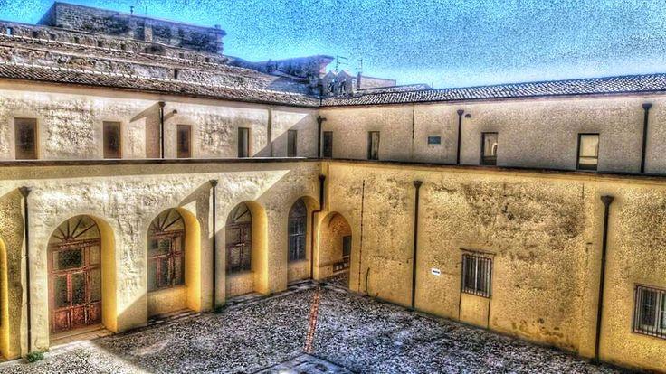 Monastero Santa Chiara _ Chiostro - La posa della prima pietra del monastero risale al 2 giugno 1610, . Fu occupato dalle suore Clarisse a partire dal 15 maggio 1668, fino alla soppressione dell'ordine nel 1861. Il grandioso complesso monastico fu costruito su preesistenti strutture di un'antica fortificazione testimoniata in modo evidente dalla tozza torretta quadrangolare, residuo di un probabile avamposto di avvistamento della cittadella sulla val Basento. Il piano superiore è…