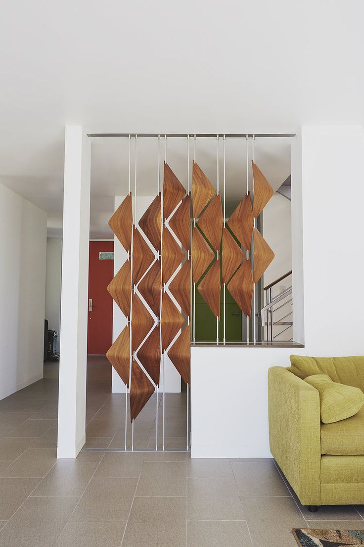 Modern room dividers, the walnut window shades act as a screen between this living room and entry way.  The screen allows for privacy and connectivity between the two spaces.  By Elish Warlop Design Studio.