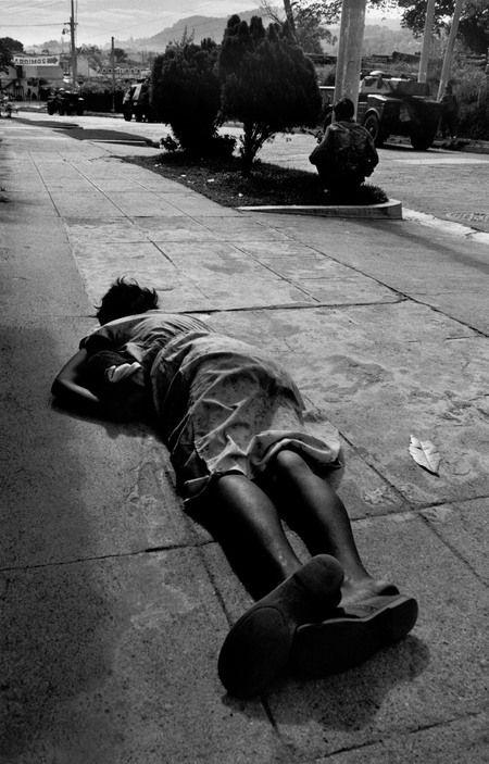 1989. A dead civilian woman lies on a sidewalk  by Larry Towell