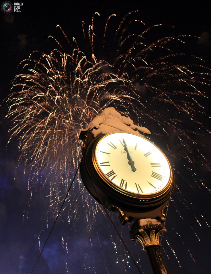 56. Fireworks explode over a clock during New Year's Day celebrations in Bucharest's Constitution Square January 1, 2011. REUTERS/Radu Sigheti