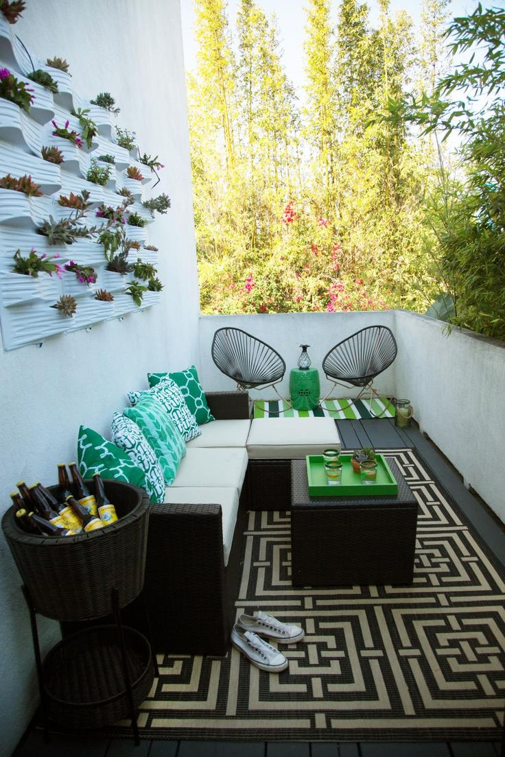 A black wicker sectional with a matching coffee table sets the tone for relaxation on this stylish patio. Green and white nautical patterned pillows pad the sofa. A textured planter mounted to the wall creates a vertical garden, and a beer basket keeps refreshments readily available.
