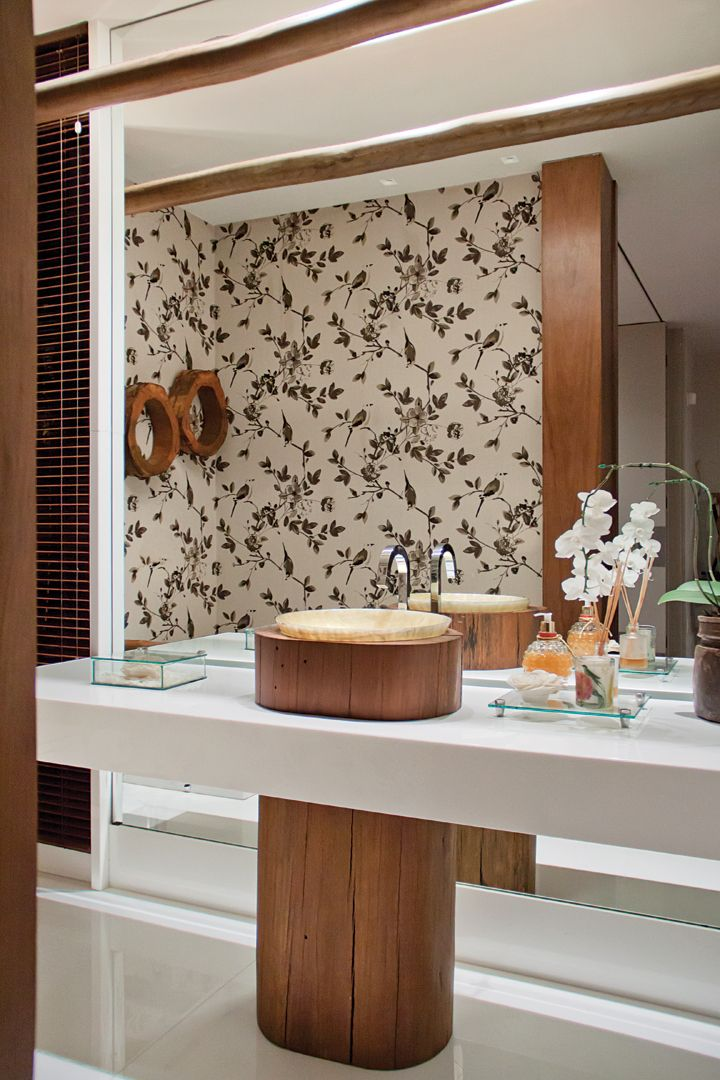 O lavabo é único, com a cuba em ônix iluminado (Marmoraria Alvorada) sobre tora de madeira (Mendo Barreto) na bancada em Nanoglass (Marmoraria Alvorada).