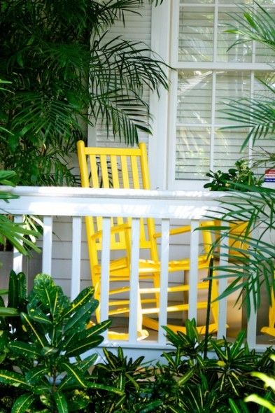 painted yellow rocking chair on porch