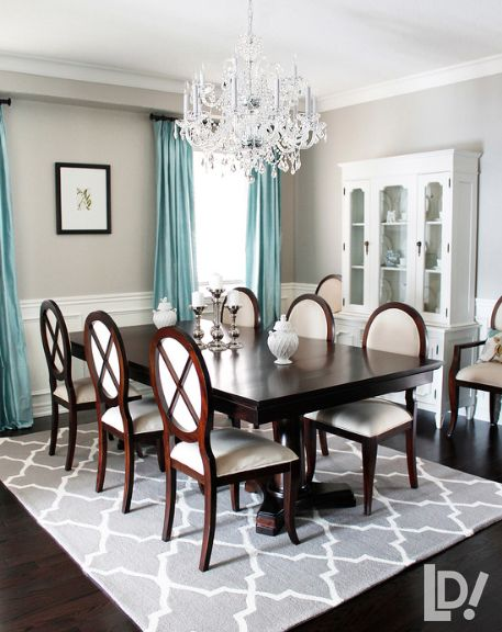 nice formal dining - dark floors, dark table, light pops like the cabinet and the rug, the wainscoting and chandelier
