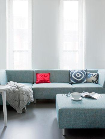 Het rode vilten kussen op deze eenvoudige grijze bank geeft een spannend effect aan de huiskamer.