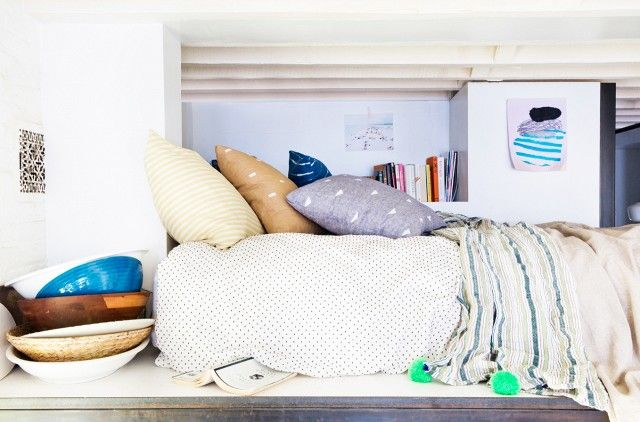 Standing up is not an option in this vertically challenged loft bedroom, but with a cool mix of printed pillows and sheets and a convenient little bookshelf, it seems like the perfect place to...