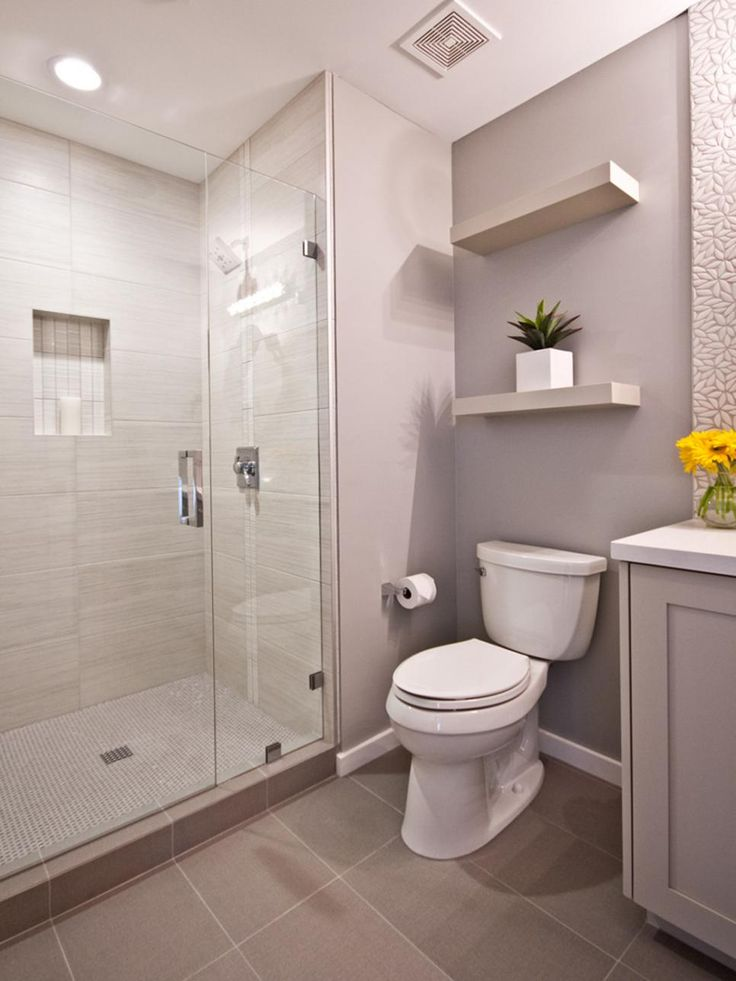 Floating shelves adorn this contemporary bathroom. A free standing shower is covered in tile and boasts the neutral color palette that flows throughout the space.