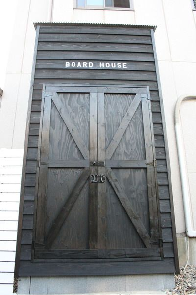 The exterior of a wooden surf shed painted in black