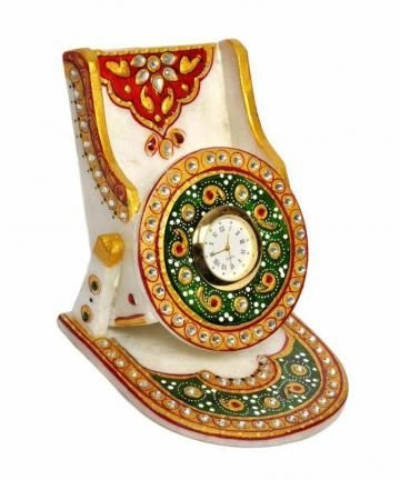 This beautiful kundan embossed mobile stand with clock, is embellished with Meenakari and kundan work that is complemented by expert enamelwork. The mobile phone holder is often decorated with intricate carvings serving as artistic gift items. Mobile phone holder is ideally designed to hold one mobile.